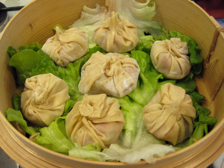 Soup dumplings on a bed of lettuce, ready to be steamed.